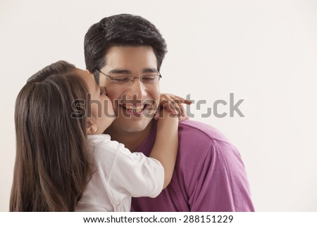 Young girl kissing her father - stock photo