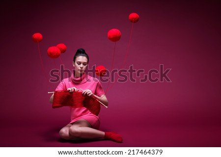Young girl knits a scarf on a red background