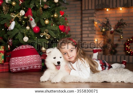 Young girl lay near Christmas tree and hug white puppy. New Year. - stock photo