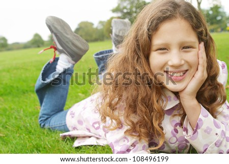 Young girl laying down on green grass in the park, smiling at the camera. - stock photo