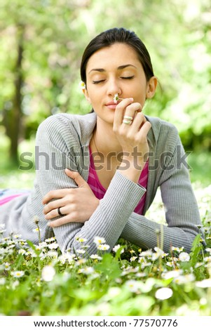 young girl laying in meadow and enjoying in smelling flowers - stock photo