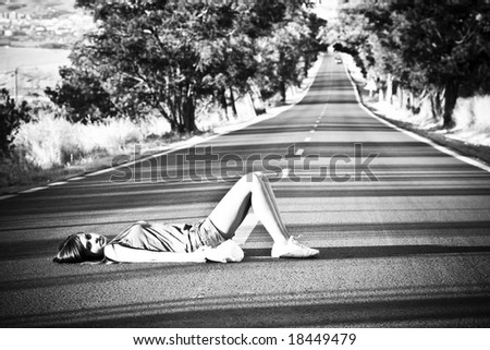 Young girl laying in the middle of nowhere. - stock photo
