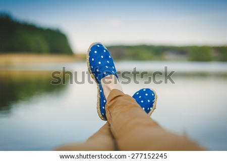 Young girl laying near the lake and resting - stock photo