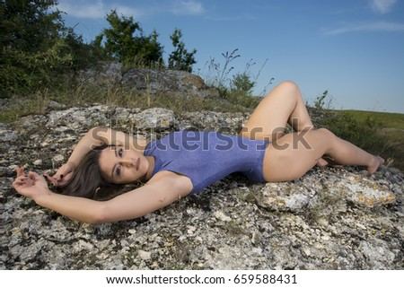 Young girl laying on a rock wearing a bodysuit