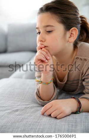 Young girl laying on couch with thoughtful look