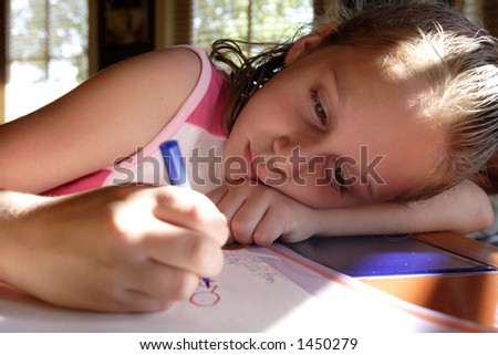 Young girl leaning her head down as she colors on a piece of paper. - stock photo