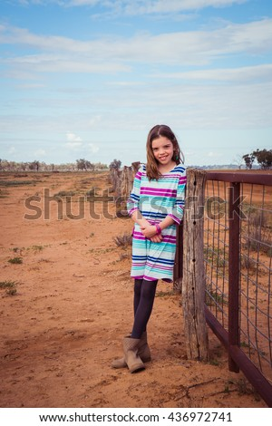 Young girl leaning on a fence in the dry drought ridden outback australia - stock photo