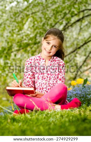 Young girl learning outdoor - spring time - stock photo