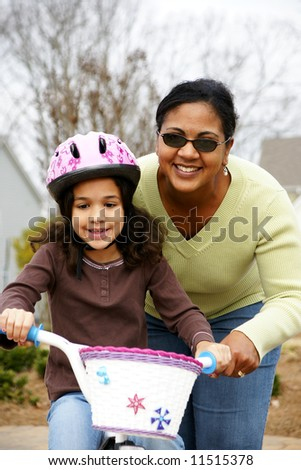 Young girl learning to ride a bike - stock photo