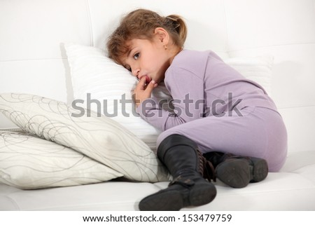 Young girl licking her fingers - stock photo