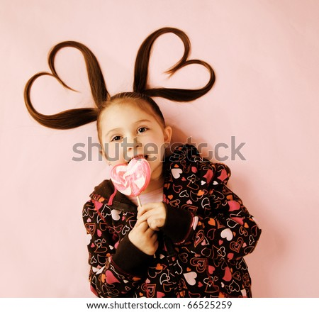 Young girl licking Valentines heart lollipop with pigtails - stock photo