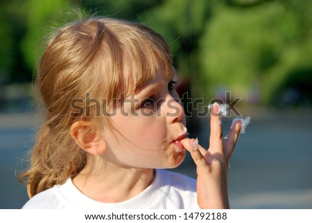 Young girl licks fingers from the cotton candy - stock photo