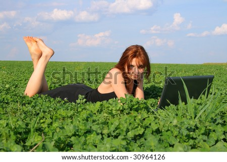 Young girl lies on clover field with laptop. Weather is sunny.