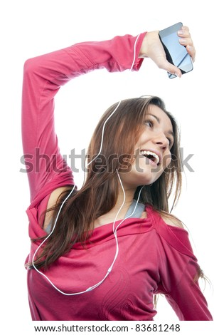 Young girl listening, enjoying music and holding cellular mp3 player in earphones on top of her head wearing dance pink top, isolated on white background