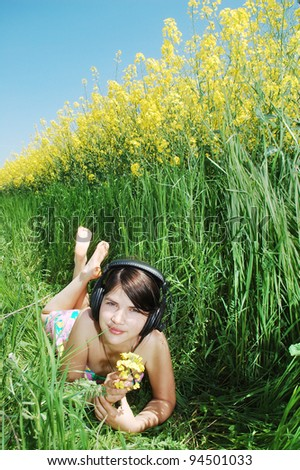young girl listening music on a springtime field. - stock photo