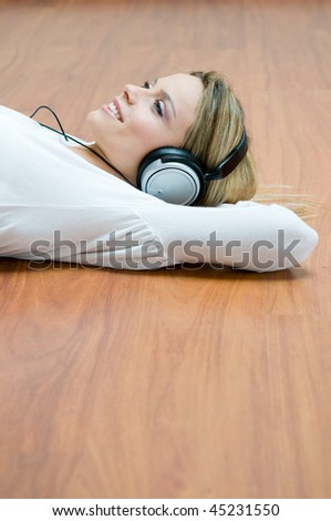 Young girl listening relaxing music with headphones lying on wooden floor - stock photo