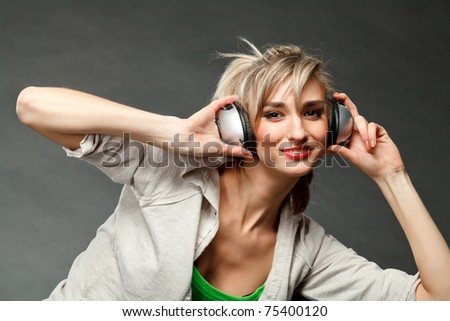 Young girl listening to music by headphones - stock photo