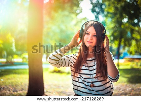 Young girl listening to music in park. Student girl outside listening to music on headphones. Happy young teenager student of Caucasian ethnicity - stock photo