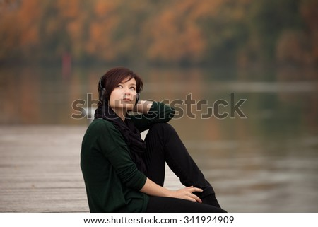 Young girl listening to the music in the autumn park