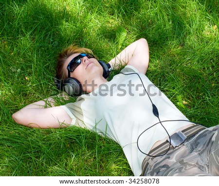 young girl listnening music on a grass