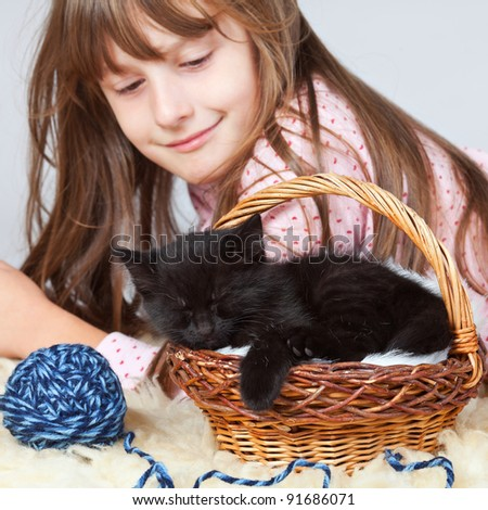 young girl looking at her sleeping kitten