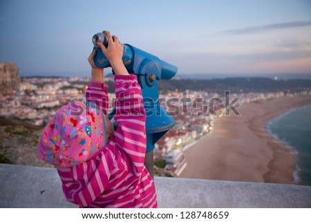 Young girl looking at Nazare Portugal with telescope from viewing area - stock photo