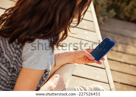 young girl looking at the screen of her mobile phone in the park - stock photo