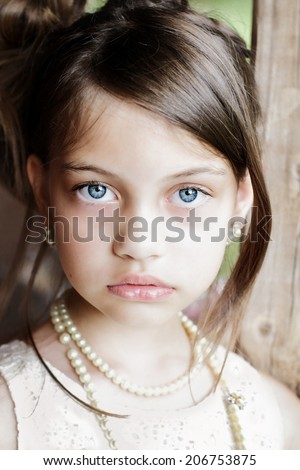 Young girl looking directly into the camera, wearing vintage pearl necklace and hair pulled back. Extreme shallow depth of field with selective focus on eyes. - stock photo