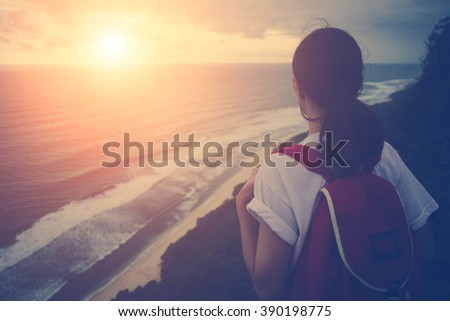 Young girl looking far away at sunset near ocean (intentional sun glare and vintage color) - stock photo
