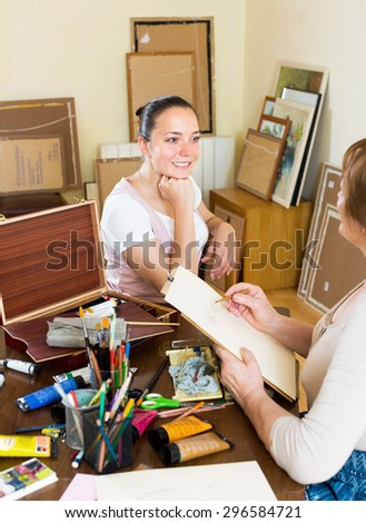 Young girl looking for elderly Artist painting his portrait at workshop - stock photo