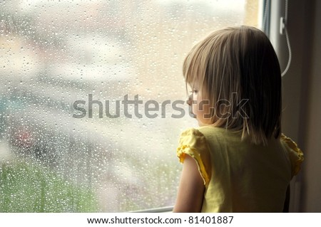 young girl looking from window - stock photo
