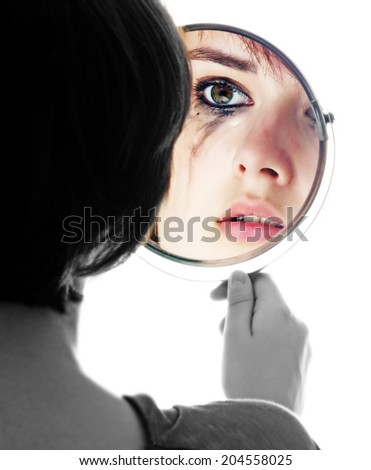 young girl looking in the mirror and crying - sensitive eyes  - stock photo