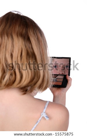 young girl looking into mirrored makeup compact