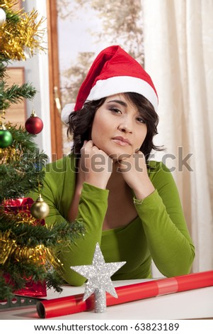 Young girl looking lonely next to a Christmas tree, wearing a Santa hat.