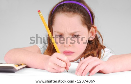 Young girl looking serious while concentrating on work - stock photo