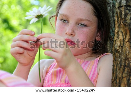 Young girl looking thoughtful or sad sitting by tree holding flower - stock photo
