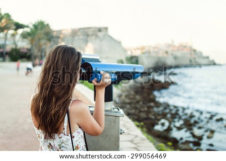 Young girl looking through a coin operated binoculars on the sea shore of Antibes, France - stock photo