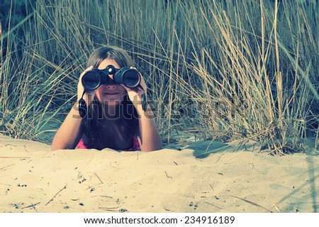 Young girl looking through binocular, low angle view  - stock photo