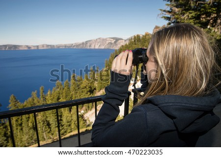 Young girl looking through binoculars at Crater Lake in Oregon,