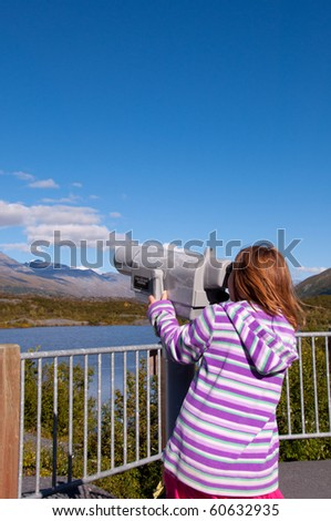 Young girl looking through distance viewer with blue sky