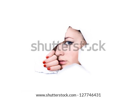 Young girl looking through hole in white paper - stock photo