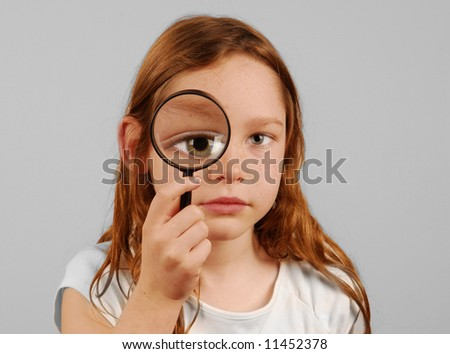 Young girl looking through magnifying glass with huge eye