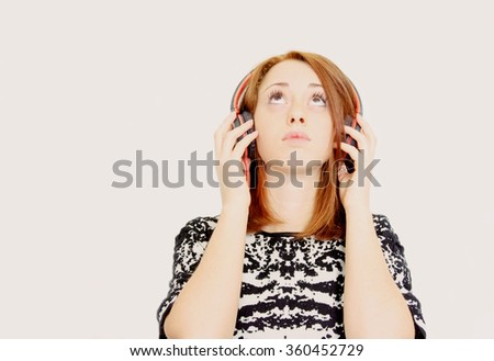 young girl looks in the high, while she is listening to music on her headphones,isolated on White background-lifestyle,technology and people concept - stock photo