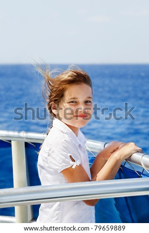 Young girl looks out from a boat rail