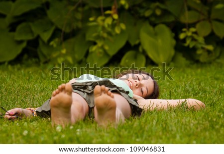 Young girl lying down on grass in the park - stock photo