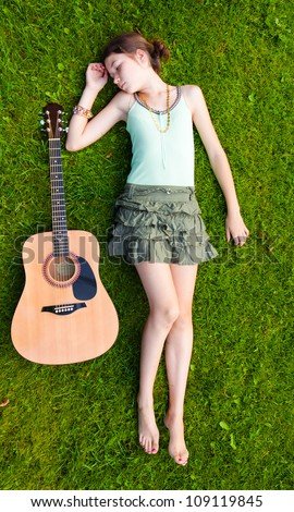 Young girl lying down on grass with a guitar - stock photo