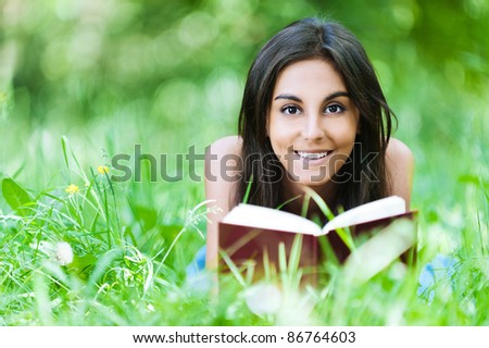young girl lying grass summer reading red book