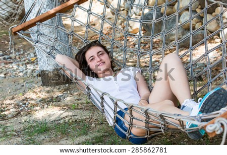 Young girl lying in a hammock in garden