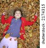 young girl lying in autumn leaves - stock photo