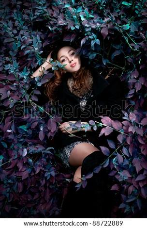 Young girl lying in fantasy bush - stock photo